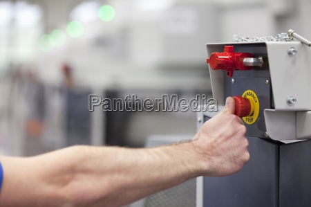 technician pressing emergency stop button on
