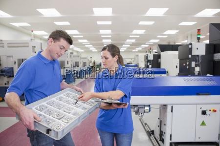 technicians examining aluminum products near lathe
