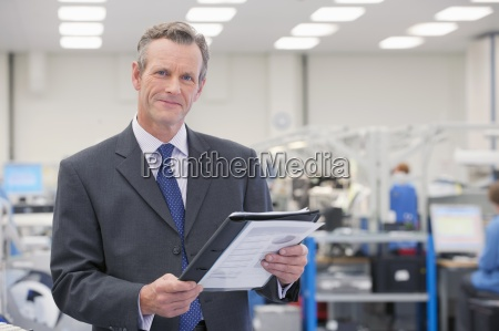 portrait of smiling businessman with paperwork