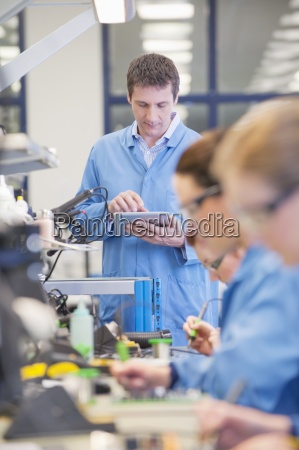 supervisor with digital tablet at production