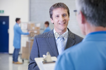 smiling businessman talking to worker with
