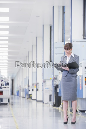 businesswoman with paperwork in manufacturing plant