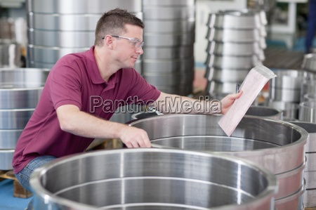 technician checking steel roller bearing inventory