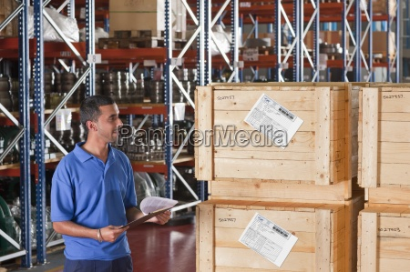 smiling worker holding clipboard and checking