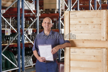 portrait of smiling worker holding paperwork