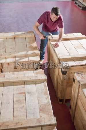 worker hammering lid on crate in