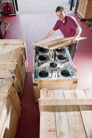 worker packing steel roller bearings in