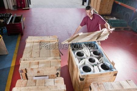 worker packing steel roller bearings in
