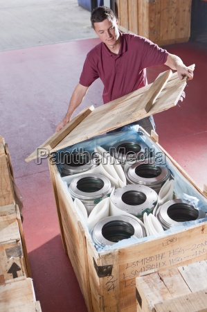 man packing steel roller bearings in