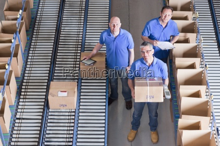portrait of smiling workers packing boxes