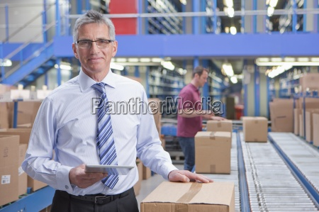 portrait of smiling businessman holding digital