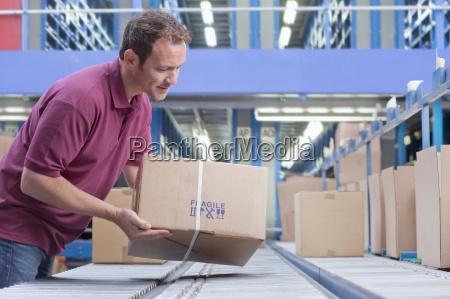 smiling man packing box on conveyor