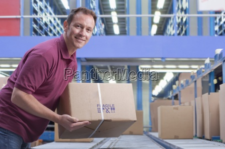 portrait of smiling man packing box