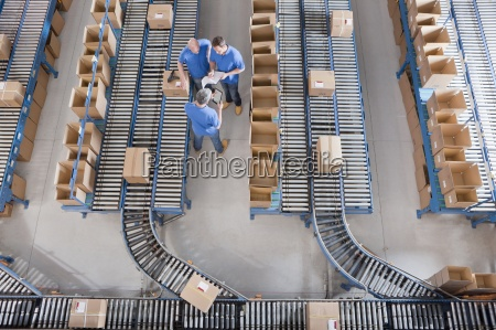 workers, meeting, among, boxes, on, conveyor - 12917788