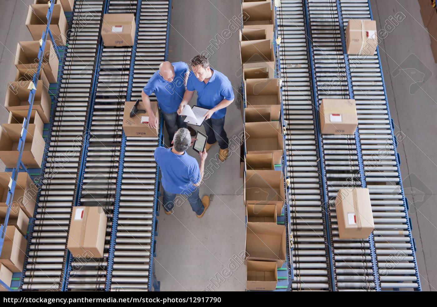 workers, meeting, among, boxes, on, conveyor - 12917790