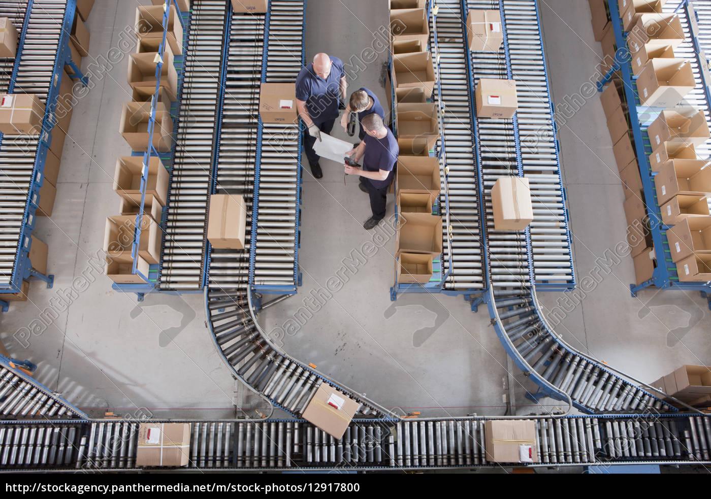 workers, meeting, among, boxes, on, conveyor - 12917800