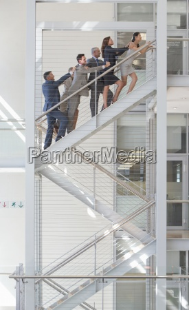 connected business people ascending stairs in