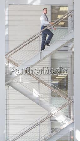 portrait of confident businessman ascending stairs