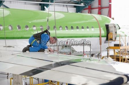 engineer inspecting wing of passenger jet