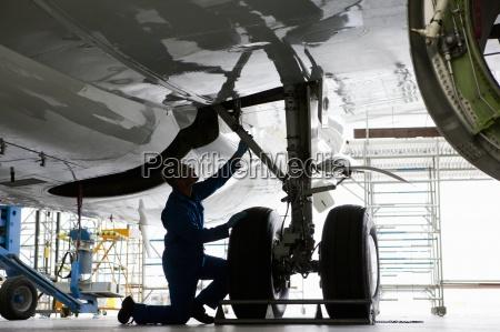 engineer inspecting landing gear on passenger