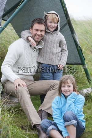 father and children standing in dunes