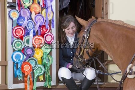 ragazza in cavallo alimentazione uniforme equestre