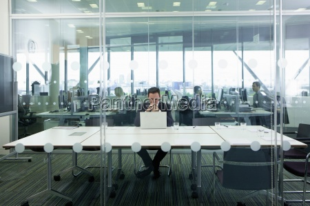 serious businessman sitting at laptop in