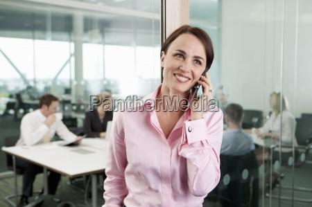 smiling brunette businesswoman talking on cell