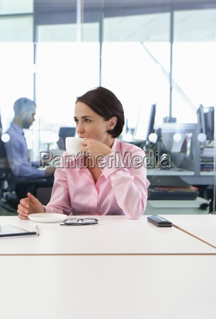 brunette businesswoman drinking coffee at conference