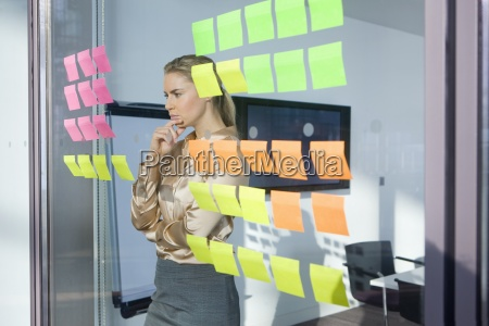 pensive businesswoman looking at adhesive notes