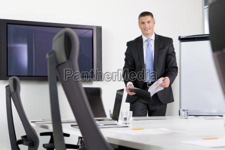 portrait of smiling businessman holding report