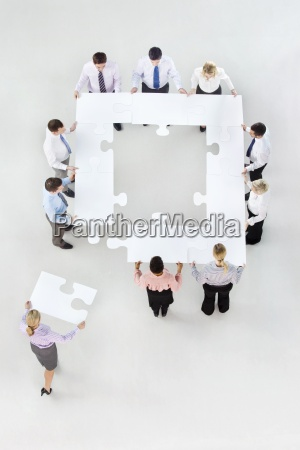business people forming square with jigsaw