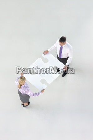 businessman and businesswoman joining large jigsaw