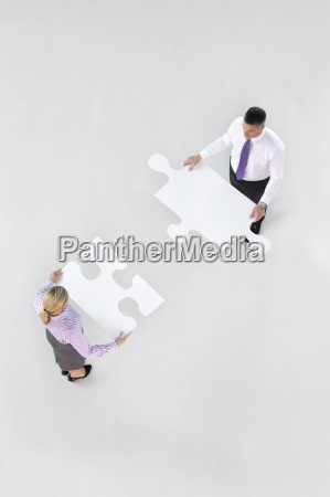 businessman and businesswoman holding large jigsaw