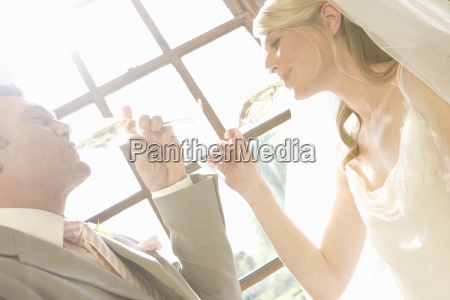 bride and groom drinking from champagne