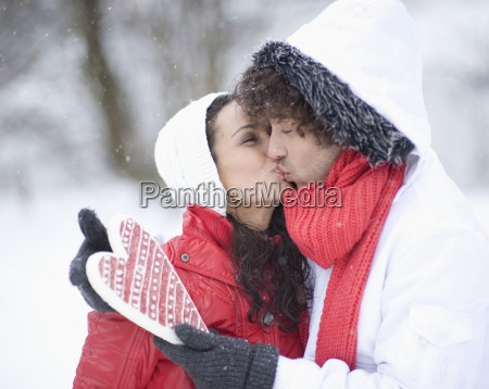 young couple holding heart kissing on