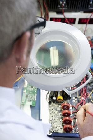 engineer examining circuit board through magnifying