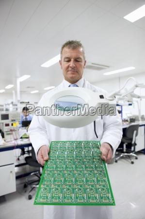engineer examining circuit board under magnifying