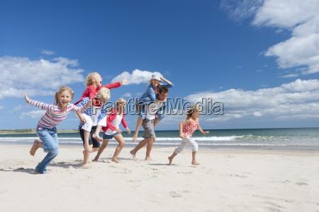 famiglia che funziona sulla spiaggia soleggiata