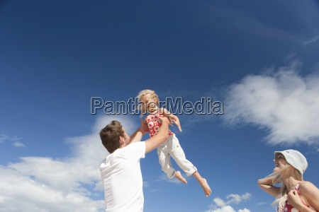 father lifting daughter against sunny blue