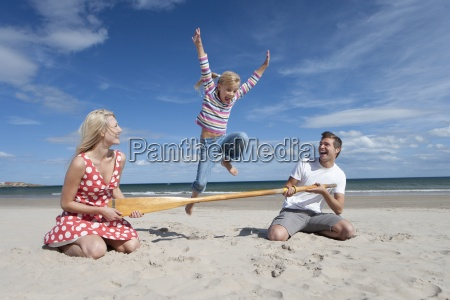 girl jumping over paddle held by