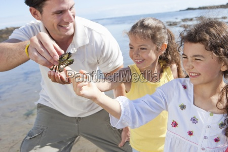 father and daughters looking at small