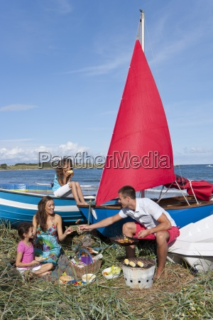 family with barbecue picnicking near boats