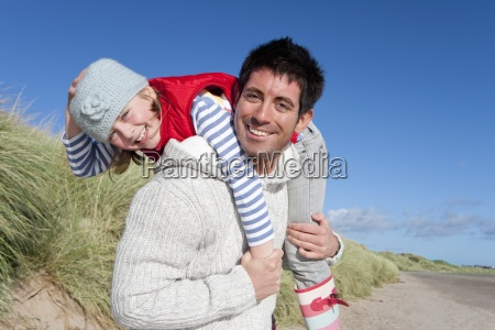 portrait of smiling father carrying daughter