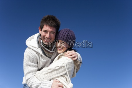 portrait of smiling couple hugging against
