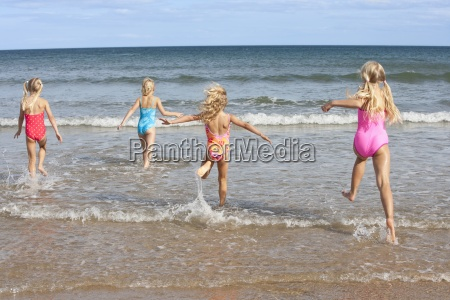 girls in bathing suits running in