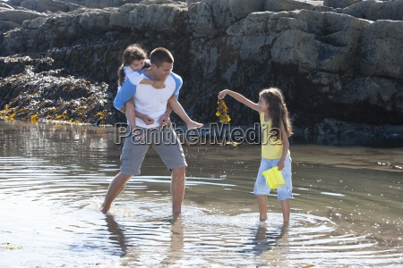 father and daughters wading in tide