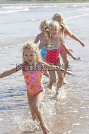 girls in bathing suits running with