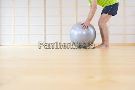 barefoot senior man lifting fitness ball
