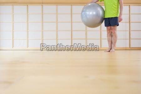 barefoot senior man holding fitness ball